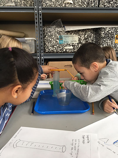students measuring in science class